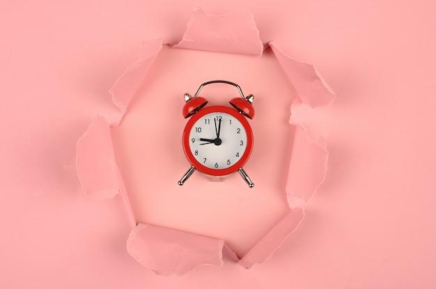 Papel rosa y reloj despertador