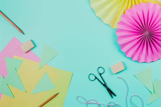 Papel de saludo lápiz; cortar con tijeras; goma de borrar y papel de flores circular sobre fondo verde azulado