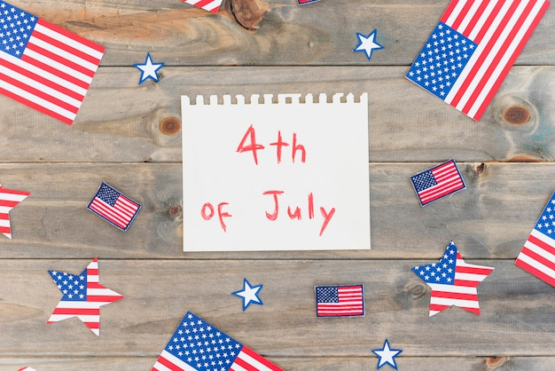 Papel con texto 4 de julio y muchas banderas de estados unidos.