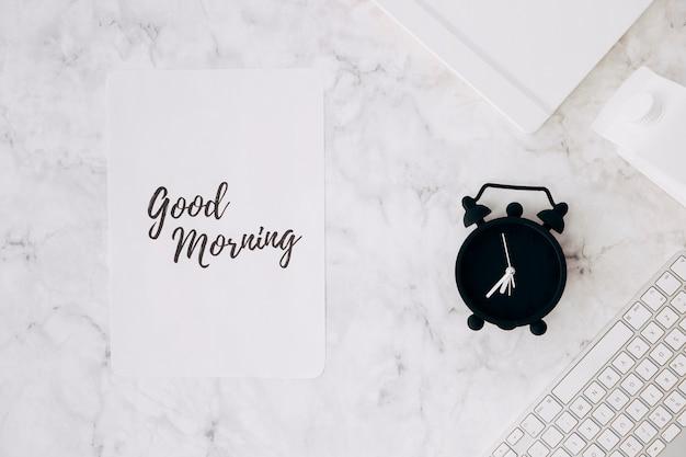 Papel con texto de buenos días; despertador; diario; cartón de leche y teclado en el escritorio