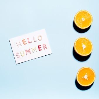 Papel con texto hola verano con mitades de naranjas jugosas.