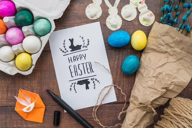 Papel con título cerca del conjunto de huevos de pascua, ramitas de sauce y origami de conejo