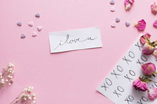 Papel con titulo junto a corazones de adorno y conjunto de flores.