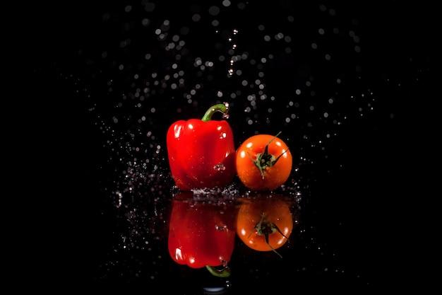 El papel y el tomate se colocan sobre el fondo negro