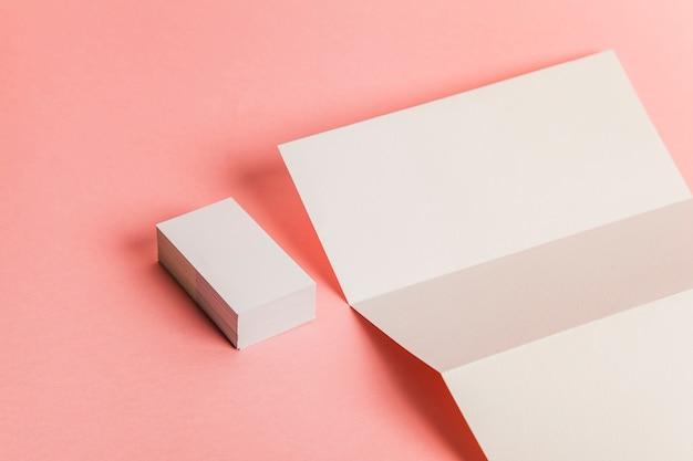 Papel tríptico a lado de montón de tarjetas de visita