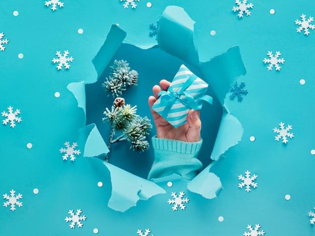 Papel turquesa plano con mano que sostiene un regalo, copos de nieve y un agujero rasgado en el medio