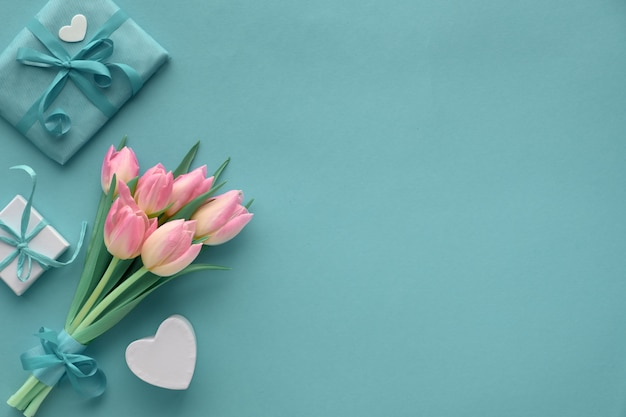 Papel turquesa de primavera con tulipanes rosados y regalos envueltos, copia