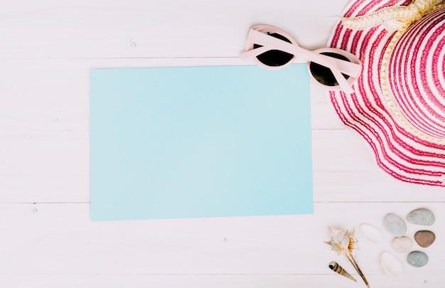 Papel vacío con accesorios de verano sobre fondo claro