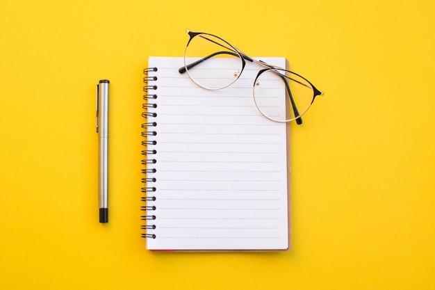 Papel vacío de las lentes y del lápiz del cuaderno en fondo amarillo con concepto de la escuela.