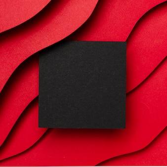 Papel vacío negro y capas onduladas de fondo rojo