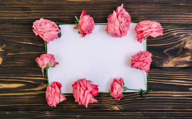 Papel vacío con rosas rosadas sobre mesa de madera con textura