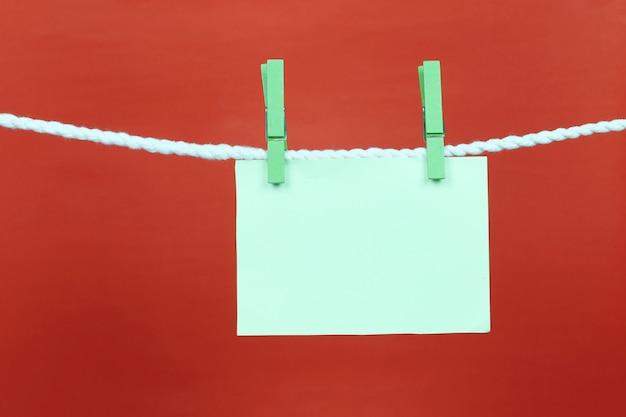 Papel verde vacío de nota colgar en el tendedero.