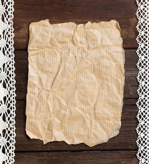 Papel viejo sobre un fondo de madera marrón con algo de decoración