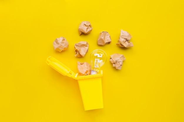 Papelera amarilla con bombilla y papel arrugado marrón sobre fondo amarillo. ideas y concepto de pensamiento creativo.