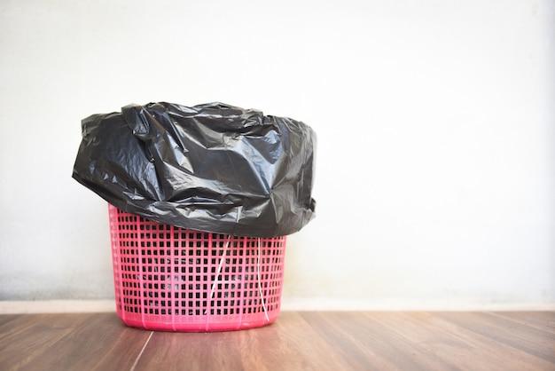 Papelera, basura y bolsa de plástico negro. papelera de reciclaje en la pared