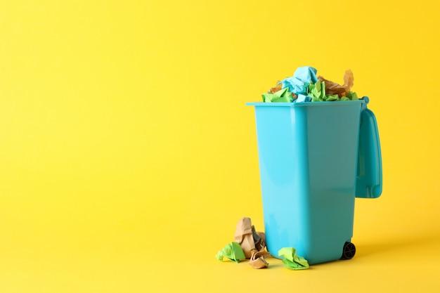 Papelera de reciclaje con basura sobre fondo amarillo, espacio para texto