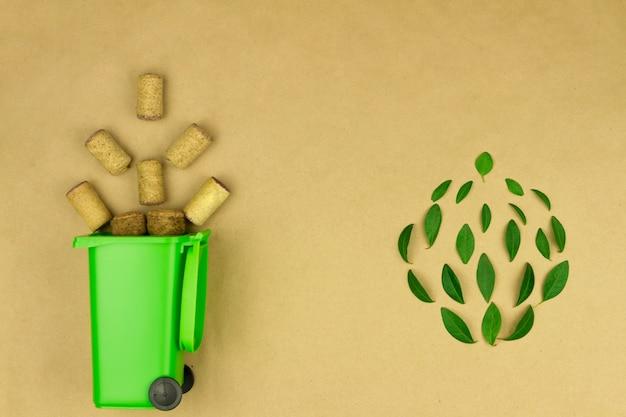 Papelera verde con ruedas con tapones de vino de madera como símbolo de reutilización de basura y concepto de reciclaje