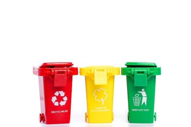 Papeleras de reciclaje amarillas, verdes y rojas con el símbolo de reciclaje aislado sobre fondo blanco.