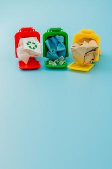Papeleras de reciclaje amarillas, verdes y rojas con el símbolo de reciclaje sobre fondo azul. mantenga la ciudad ordenada, deja el símbolo de reciclaje. concepto de protección de la naturaleza
