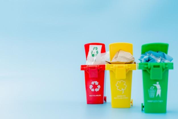 Papeleras de reciclaje amarillas, verdes y rojas con símbolo de reciclaje sobre fondo azul. mantenga la ciudad ordenada, deja el símbolo de reciclaje. concepto de protección de la naturaleza.