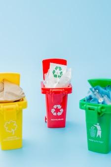 Papeleras de reciclaje amarillas, verdes y rojas con símbolo de reciclaje sobre fondo azul.