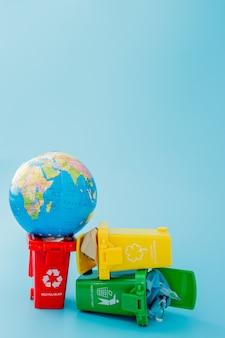 Papeleras de reciclaje amarillas, verdes y rojas con el símbolo de reciclaje en la superficie azul. mantenga la ciudad ordenada, deja el símbolo de reciclaje. concepto de protección de la naturaleza