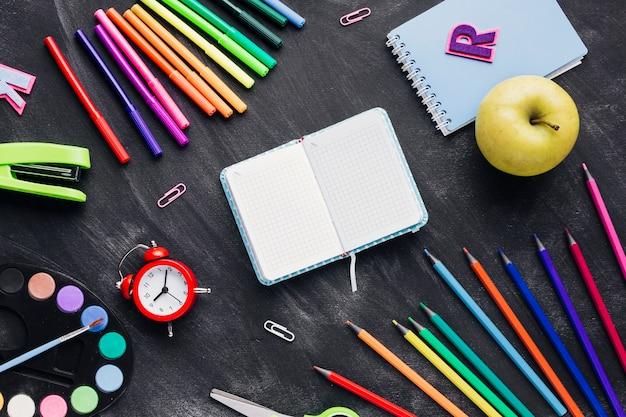 Papelería brillante, reloj y manzana alrededor de cuaderno sobre fondo gris