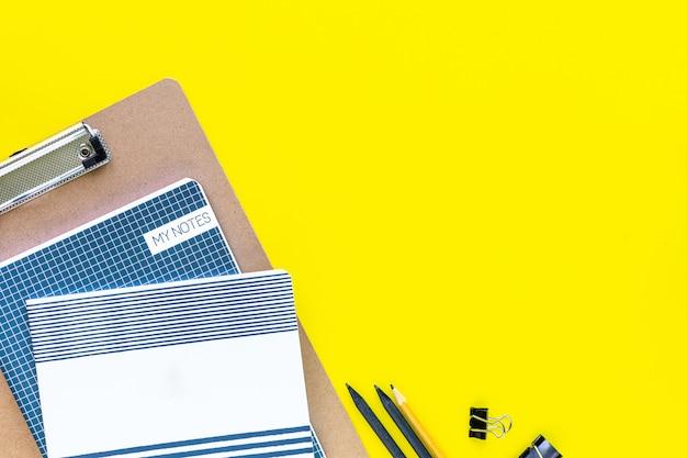 Papelería de colores surtidos para la escuela y la oficina sobre fondo amarillo con copyspace.