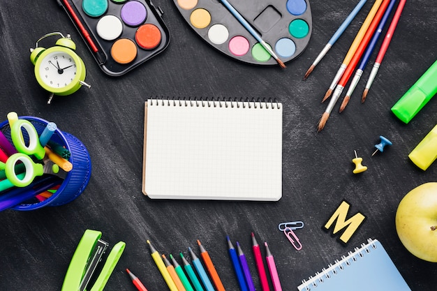Papelería colorida, pinturas y reloj que rodea el cuaderno sobre fondo gris