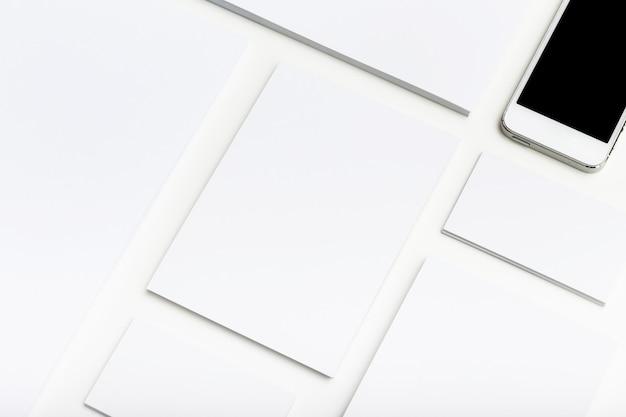 Papelería corporativa en blanco y teléfono inteligente en mesa