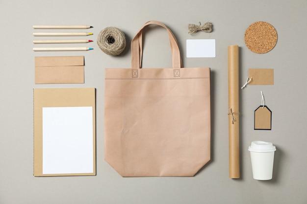 Papelería corporativa, bolso de mano y taza de papel sobre fondo gris.