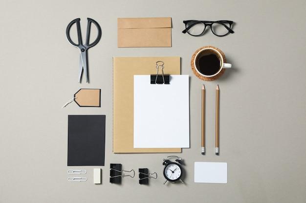 Papelería corporativa, gafas y despertador sobre fondo gris.