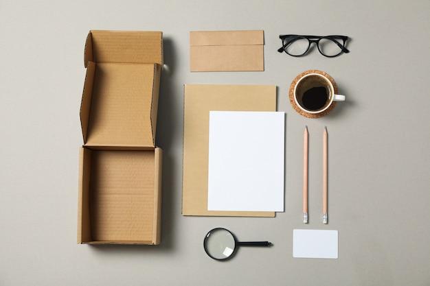 Papelería corporativa, gafas y lupa sobre fondo gris.