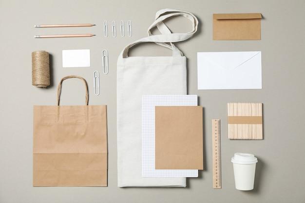 Papelería corporativa con papel y bolsa sobre fondo gris.