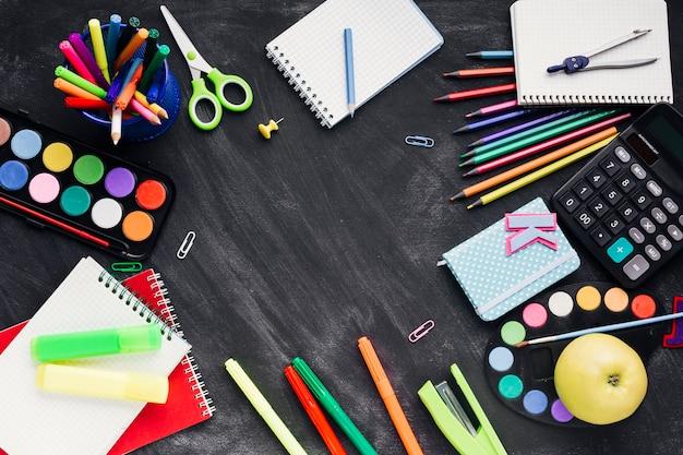Papelería creativa colorida, calculadora y manzana sobre fondo oscuro