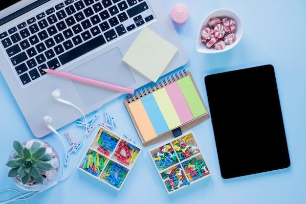 Papelería y dulces cerca de la tableta y computadora portátil