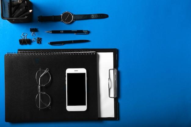 Papelería elegante con teléfono móvil y reloj en superficie de color