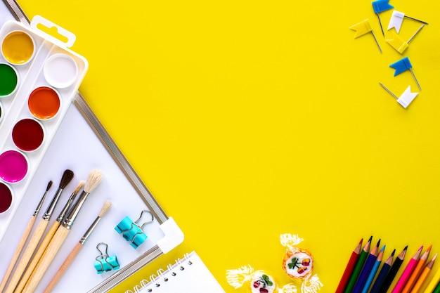 Papelería escolar de colores sobre fondo amarillo con copyspace.