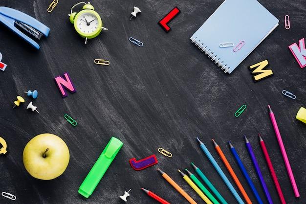 Papelería escolar con manzana y reloj despertador esparcidos en pizarra