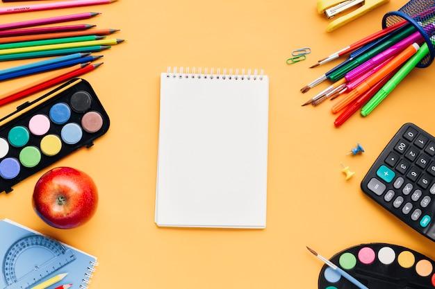 Papelería escolar multicolor dispersa alrededor de la libreta en blanco en el escritorio amarillo