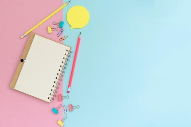 Papelería escolar sobre un fondo rosa y azul. volver a la escuela creativa, espacio de trabajo de oficina con suministros