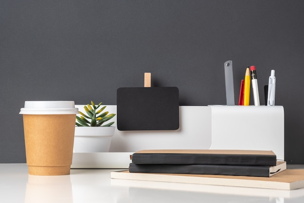 Papelería de oficina moderna en mesa blanca y pared gris oscuro