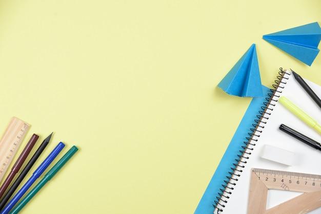 Papelería de oficina y papel doblado sobre fondo amarillo.