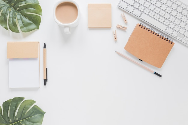 Papelería y teclado en mesa blanca con hojas verdes y taza de café