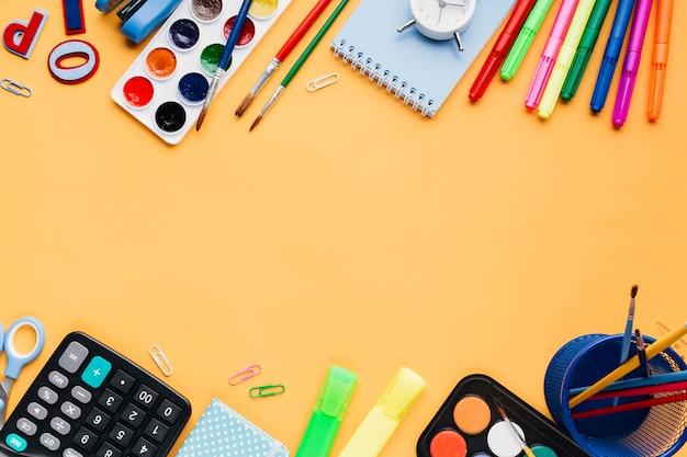 Papelería y útiles de oficina en mesa naranja.