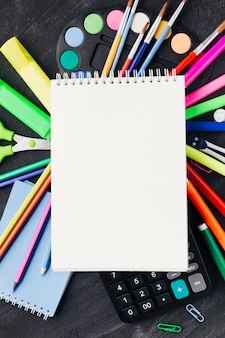 Papelería vibrante y calculadora bajo cuaderno blanco
