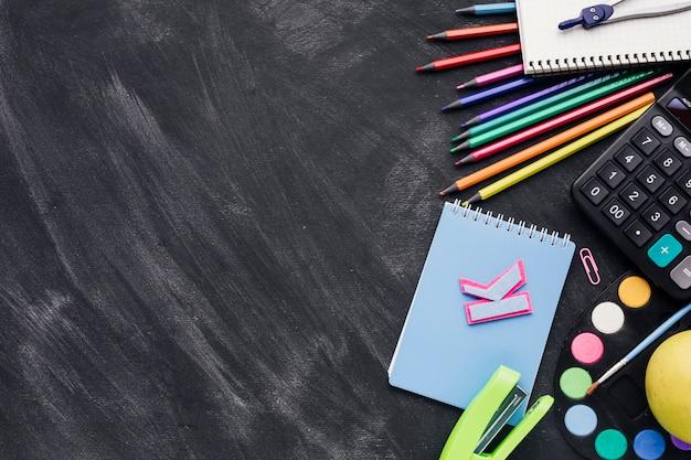 Papelería vibrante con cuaderno, calculadora y divisor sobre fondo oscuro