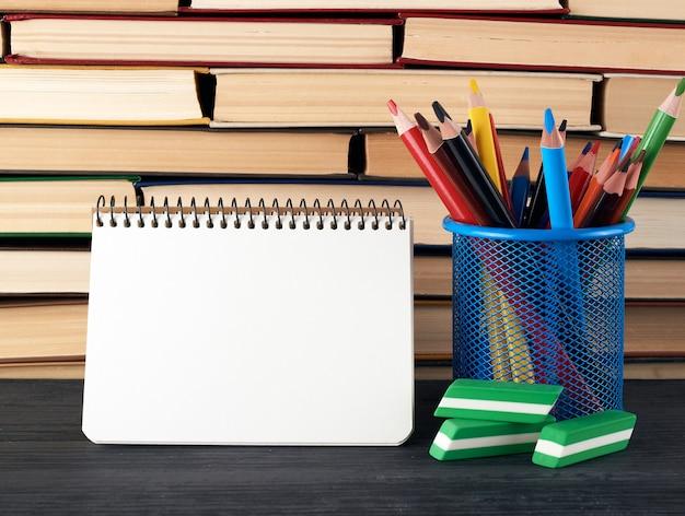 Papelería de vidrio azul con lápices de madera multicolores, cuaderno espiral abierto