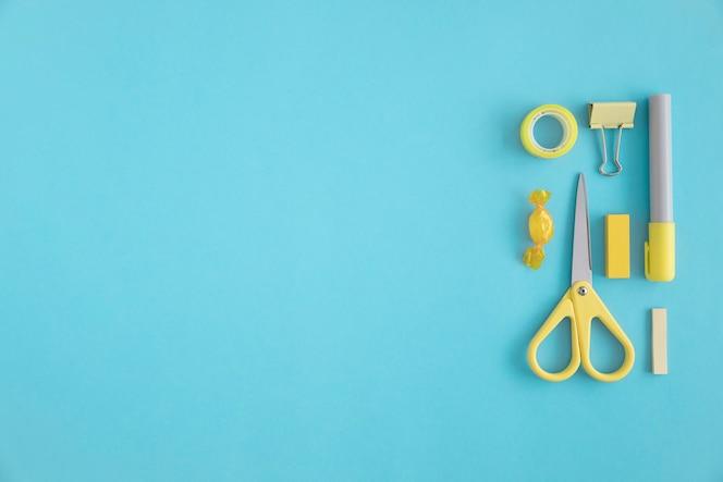 Papelería y caramelos amarillos sobre fondo azul