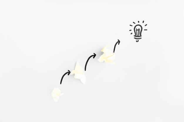 Papeles arrugados con flechas direccionales apuntando hacia la bombilla de luz sobre fondo blanco